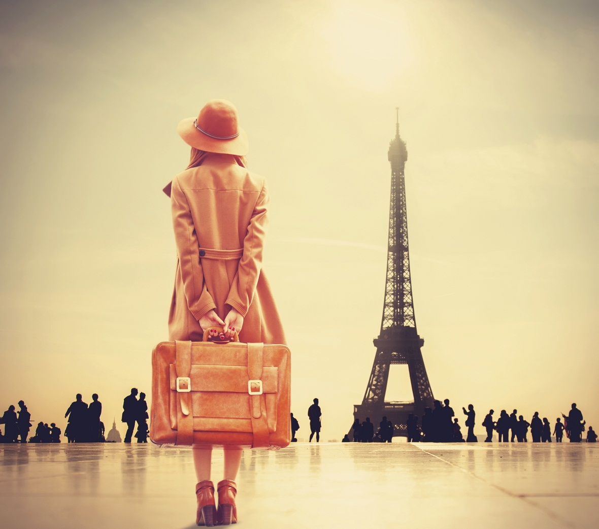 girl with suitcase facing the Eiffel Tower