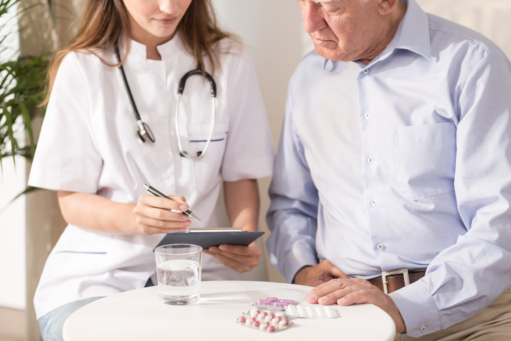 doctor writing prescription for elderly male patient