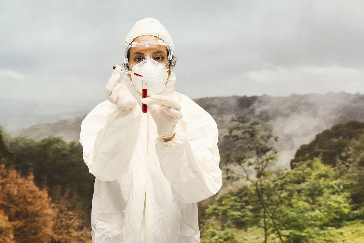 scientist with test tube dressed in hazmat suit
