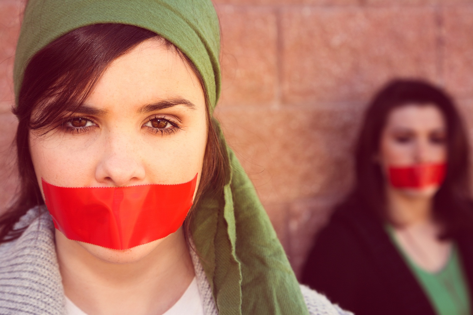 two women with red tape across their mouths