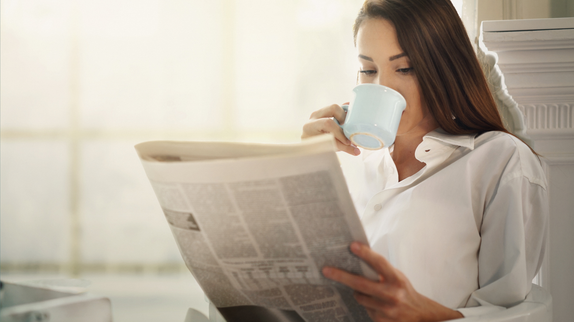woman sipping coffee and reading the newspaper