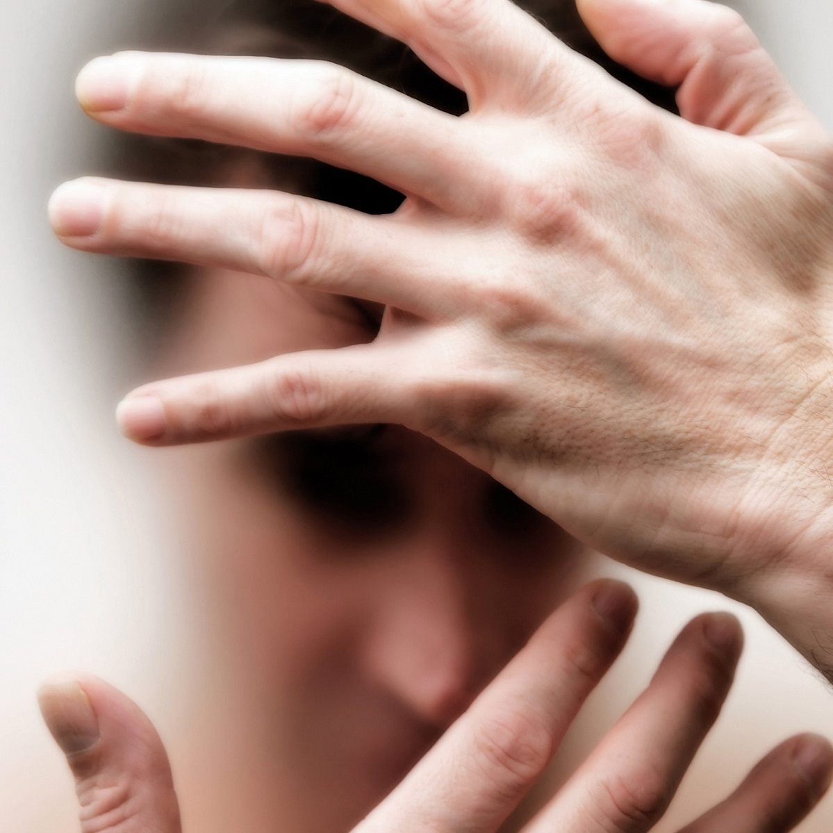 man in pain with hands over face