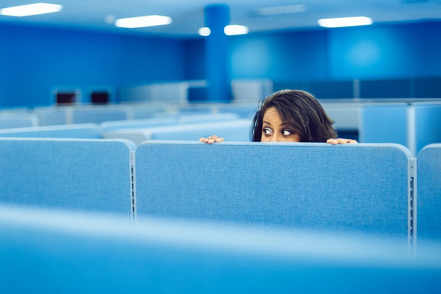 woman peeking over office divider