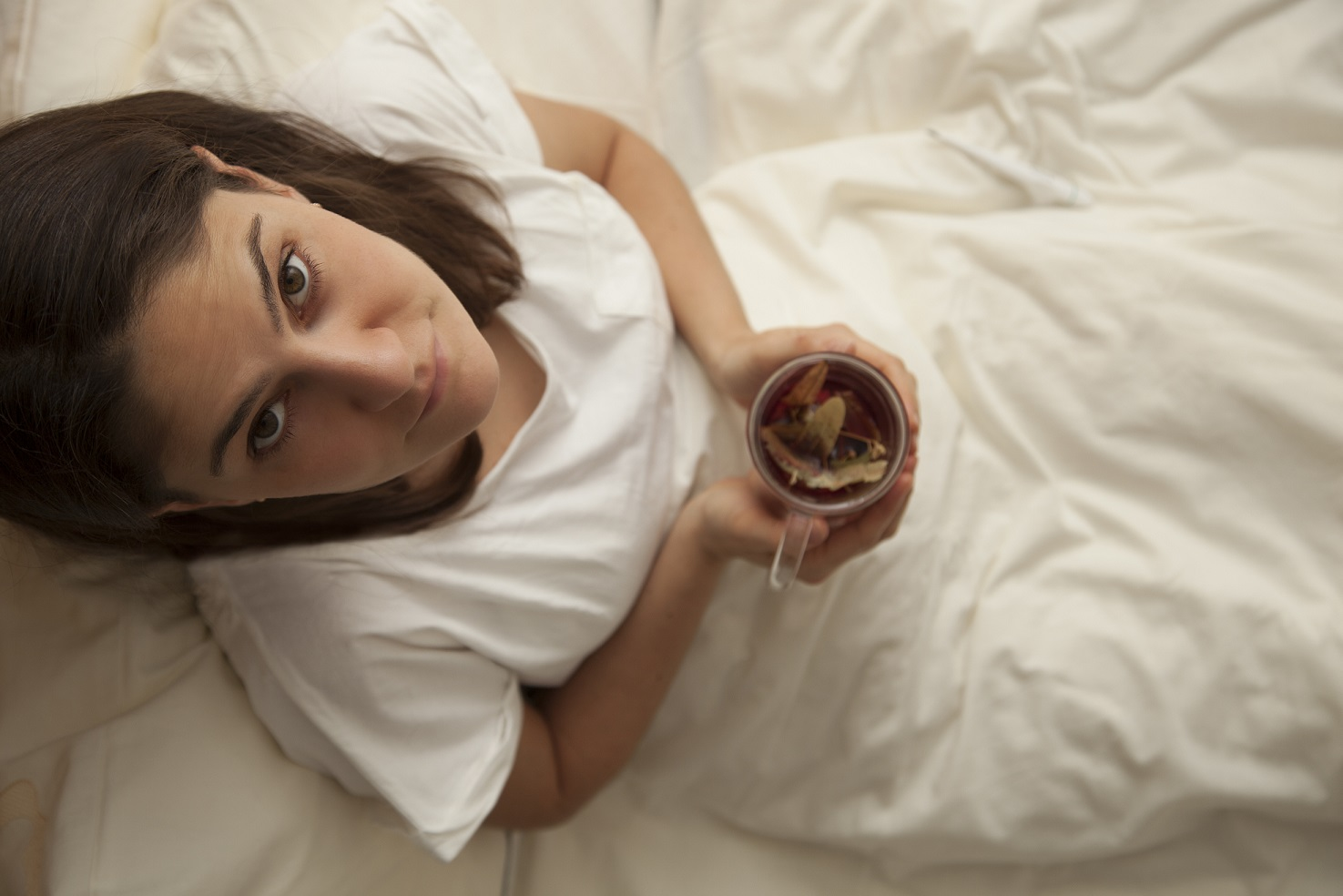 woman laying in bed with cup of hot tea